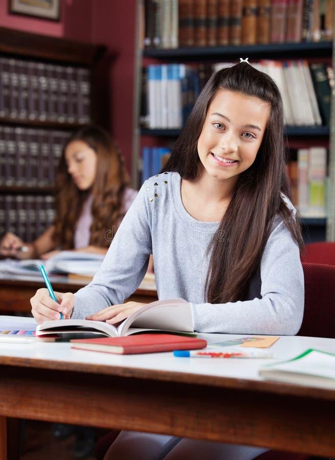 Tonårs- le för skolflicka arkivfoton