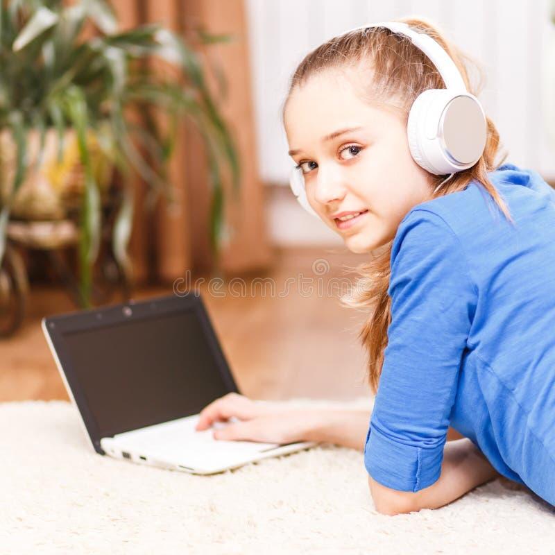Tonårs- le flicka som använder bärbara datorn på golvet arkivfoton