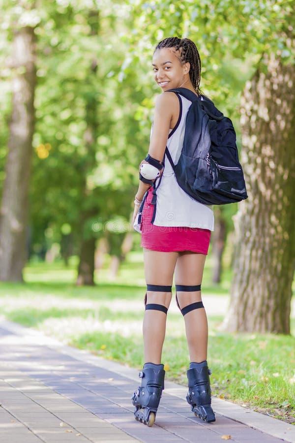 Tonårs- livsstilbegrepp och idéer Kvinnlig tonåring för Sportive afrikansk amerikan som har gyckel på rullskridskor royaltyfria bilder