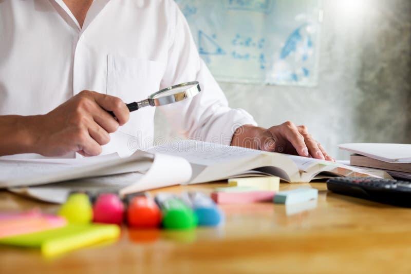 Tonårs- mansammanträde vid trätabellläsning och handstil på anteckningsboken i ett klassrum framme av ett bräde med formler arkivfoton