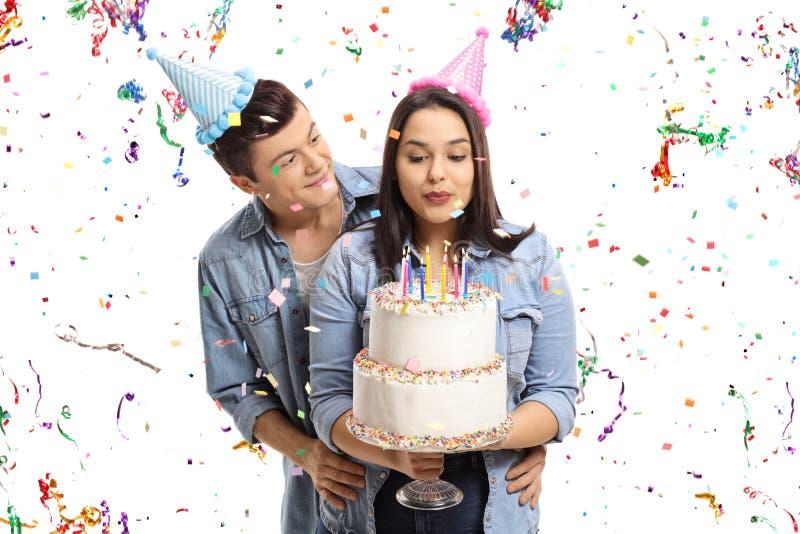 Tonårs- par med en flyin för banderoller för födelsedagkaka och konfetti royaltyfria foton