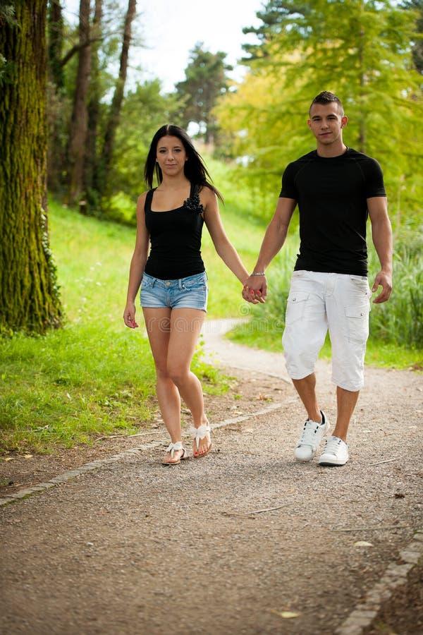Tonårs- par som går på en eftermiddag för sen sommar parkerar in arkivbild