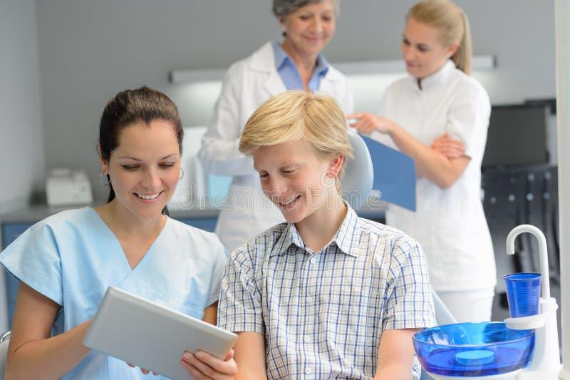 Tonårs- patient med den yrkesmässiga tandläkarepunktminnestavlan royaltyfri fotografi