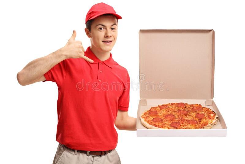 Tonårs- pizzaleveranspojke som rymmer en pizzaask och gör en appell royaltyfri foto
