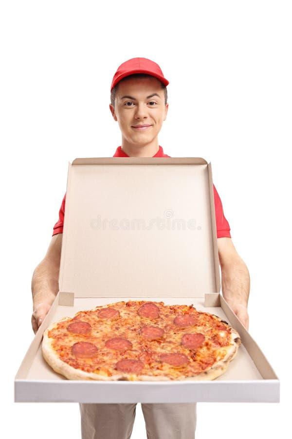Tonårs- pizzaleveranspojke som visar en pizza royaltyfri foto