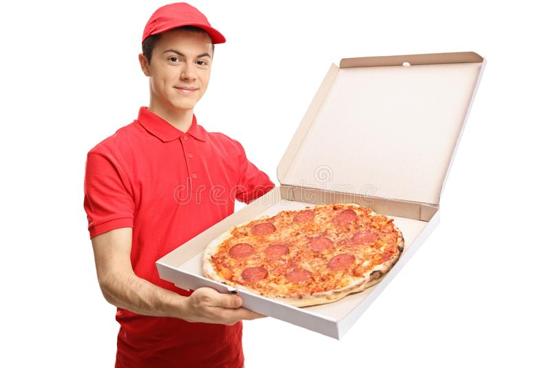 Tonårs- pizzaleveranspojke som visar en pizza inom en ask royaltyfria bilder