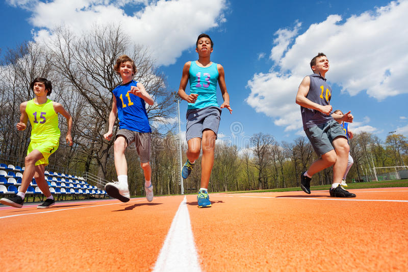 Tonårs- pojkar för friidrott som kör på löparbanan arkivfoto