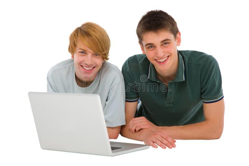Tonårs- pojkar med bärbar dator som ner ligger royaltyfri bild
