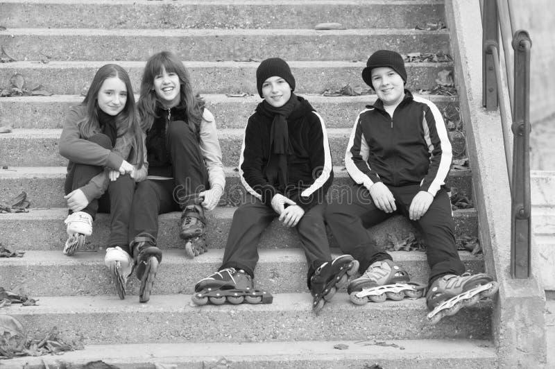 Tonårs- pojkar och flickor i rullskridskor som sitter på trappa arkivbild
