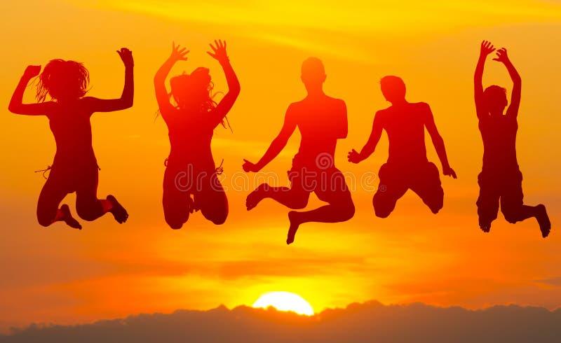 Tonårs- pojkar och flickor som högt hoppar i luften mot solnedgång arkivbild