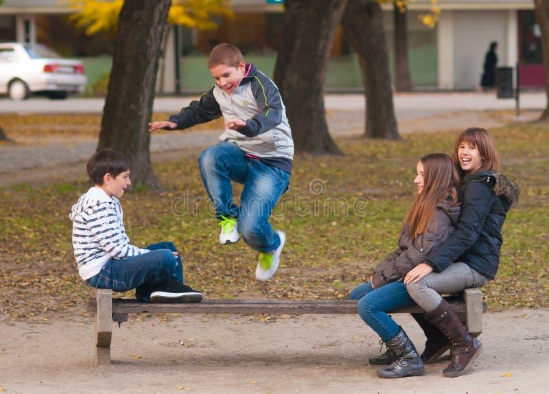 Tonårs- pojkar och flickor som har gyckel i parken royaltyfri fotografi