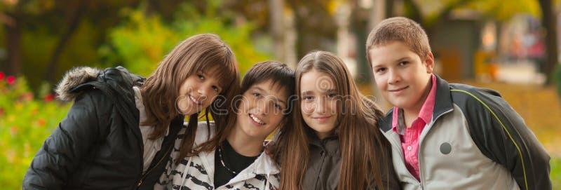 Tonårs- pojkar och flickor som har gyckel i parkera på härlig höstdag royaltyfria bilder