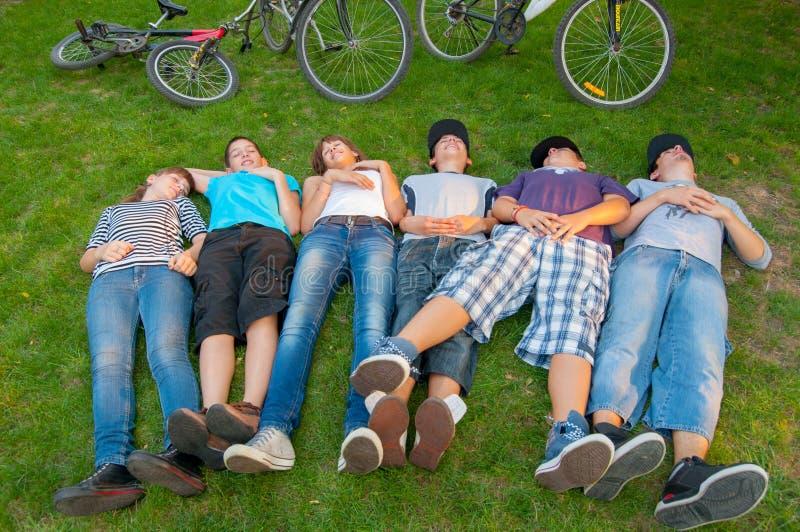 Tonårs- pojkar och flickor som ligger i gräset royaltyfri fotografi