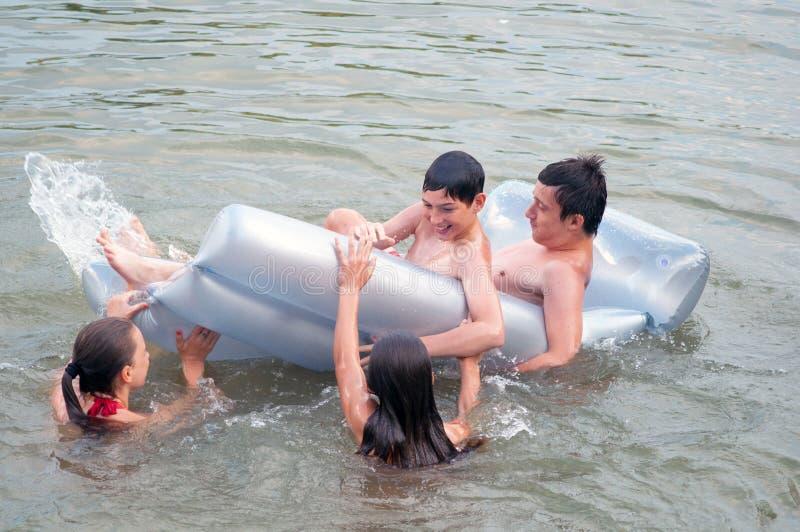 Tonårs- pojkar och flickor som simmar och spelar i floden i sommar arkivfoton