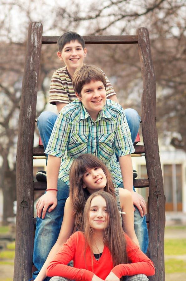 Tonårs- pojkar och flickor som in sitter, parkerar på härlig vårdag arkivfoto
