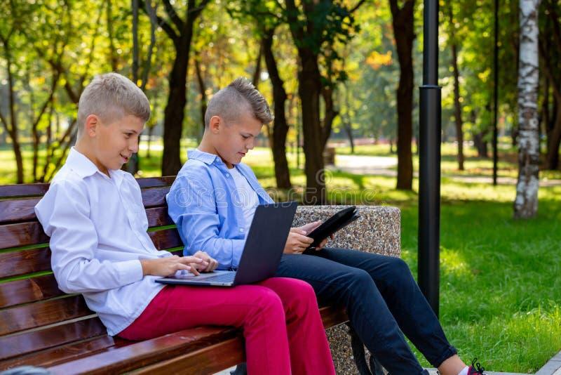 Tonårs- pojkar parkerar på bänken genom att använda bärbara datorn och den Digital minnestavlan arkivfoton