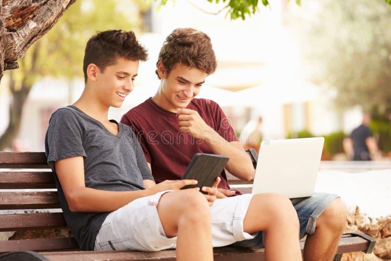 Tonårs- pojkar parkerar på bänken genom att använda bärbara datorn och den Digital minnestavlan arkivbild