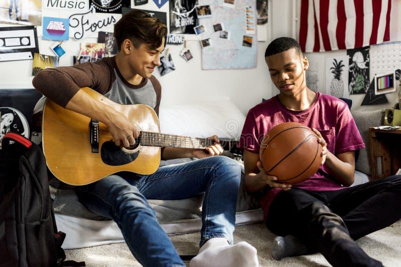 Tonårs- pojkar som ut hänger i ett sovrummusik- och sporthobbybegrepp royaltyfri fotografi