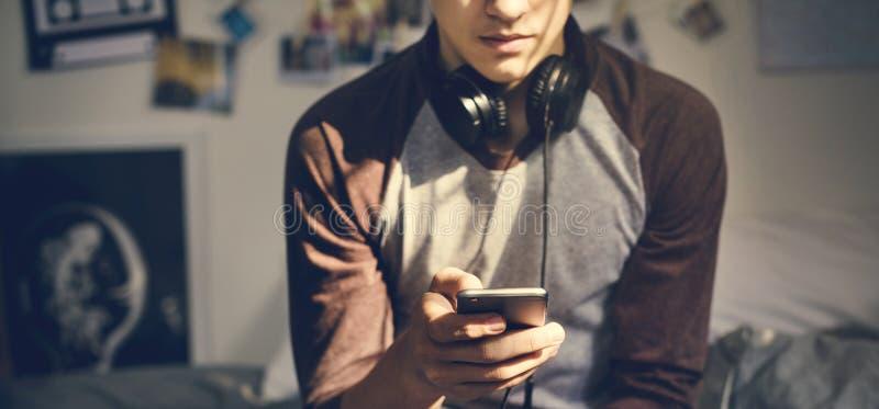 Tonårs- pojke i ett sovrum som lyssnar till musik till och med hans smartpho royaltyfria foton