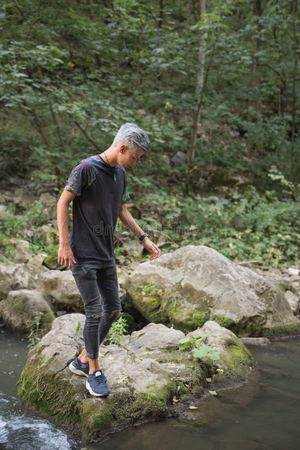Tonårs- pojke i natur på kusterna av en flod royaltyfria foton
