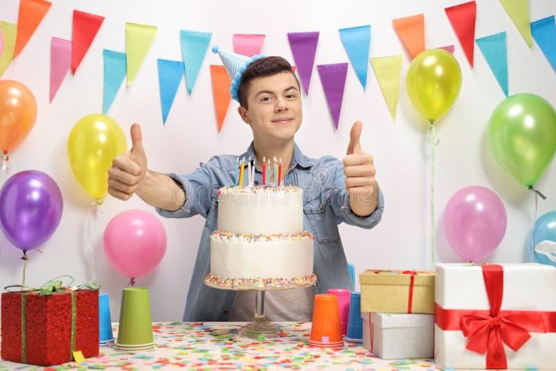 Tonårs- pojke med en födelsedagkaka royaltyfri bild
