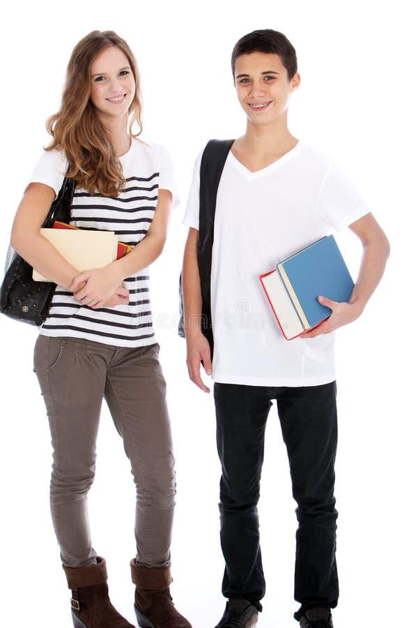 Tonårs- pojke och flicka med högskolaböcker fotografering för bildbyråer