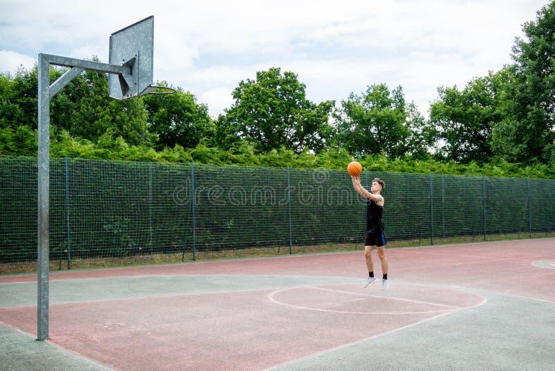 Tonårs- pojke på en basketdomstol arkivfoto