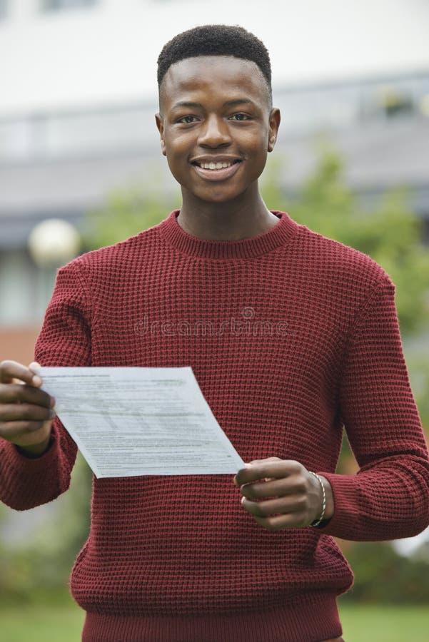 Tonårs- pojke som är lycklig med bra examenresultat royaltyfri fotografi