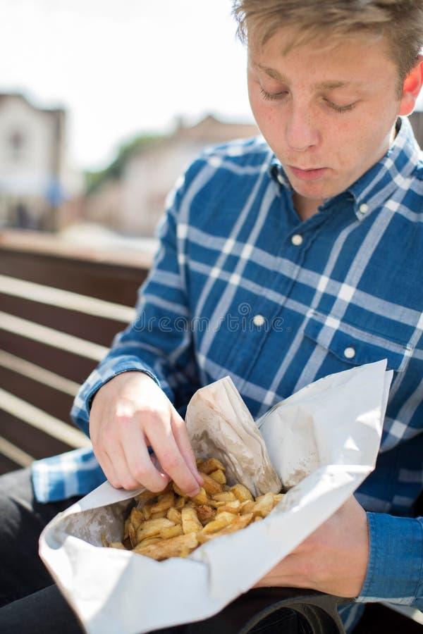 Tonårs- pojke som äter pommes frites som utomhus sitter på bänk royaltyfria bilder