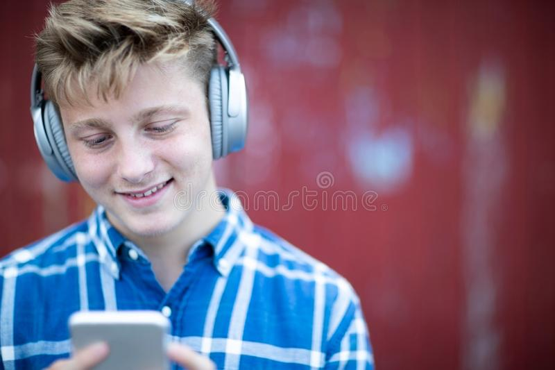 Tonårs- pojke som bär trådlös hörlurar och lyssnar till musik i stads- inställning arkivfoton