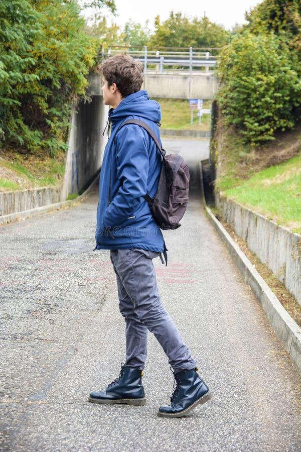 Tonårs- pojke som bara går i gata med ryggsäcken royaltyfri foto