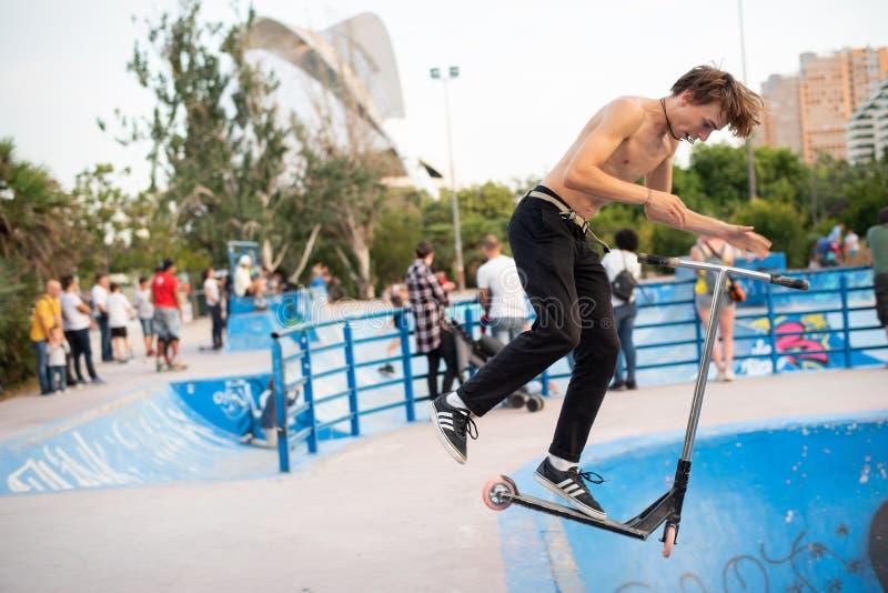 Tonårs- pojke som hoppar med hans sparkcykel på skateparken i Valencia, Spanien royaltyfri fotografi