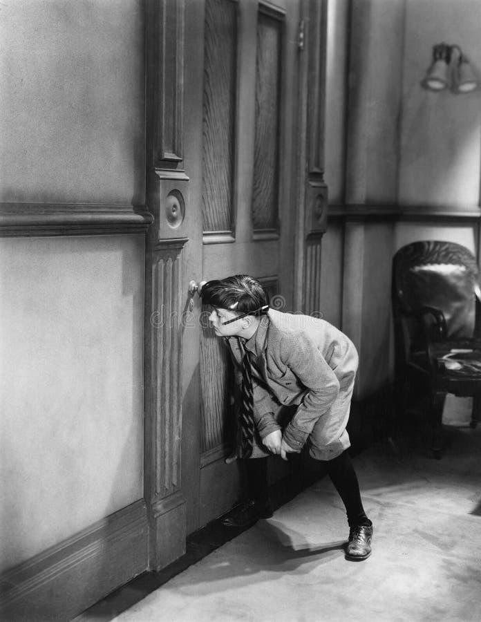 Tonårs- pojke som kikar till och med nyckelhålet (alla visade personer inte är längre uppehälle, och inget gods finns Leverantörg arkivfoto