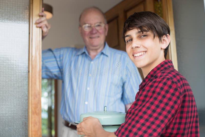 Tonårs- pojke som kommer med mål för äldre manlig granne arkivbild