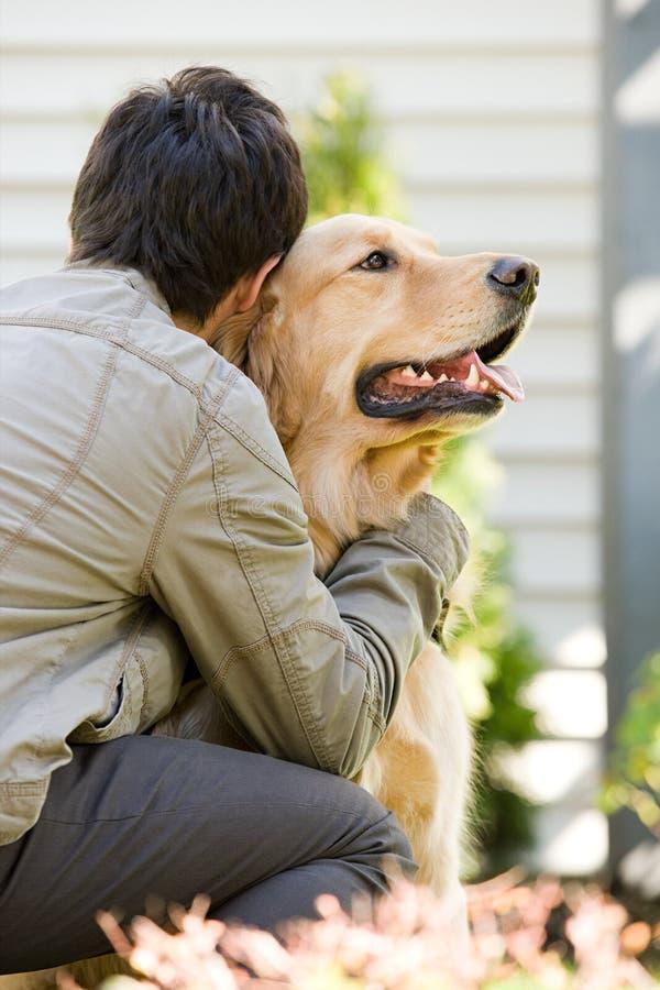 Tonårs- pojke som kramar den älsklings- hunden arkivfoton