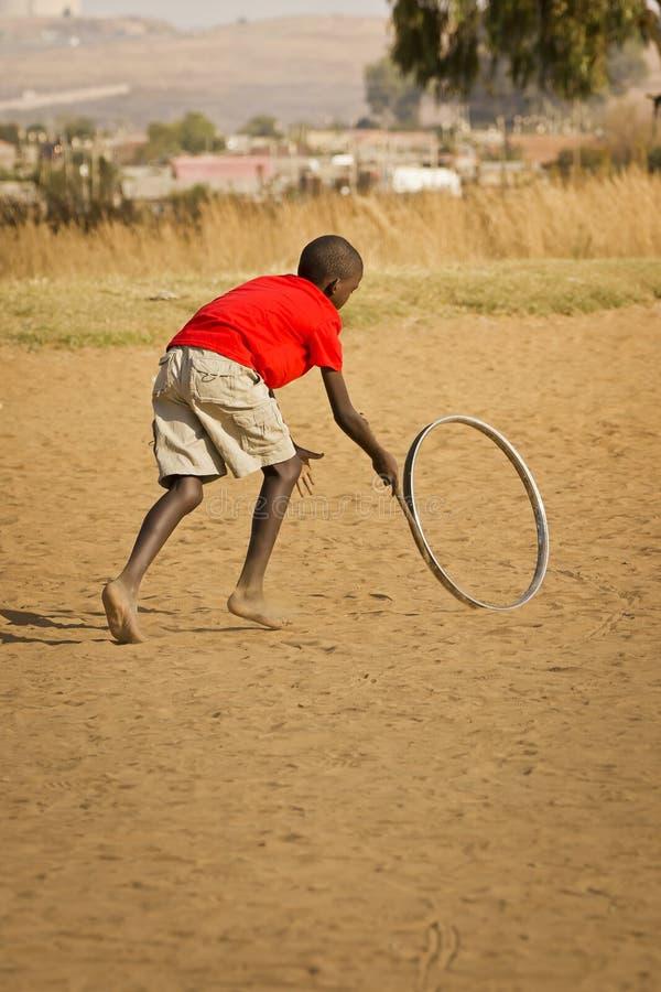 Tonårs- pojke som leker med hjulet - bakre sikt arkivbild