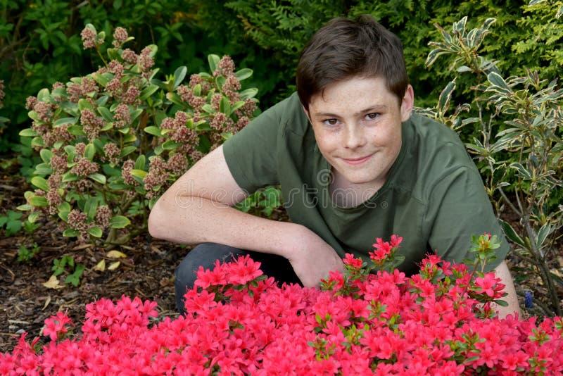 Tonårs- pojke som poserar för foto i trädgården fotografering för bildbyråer