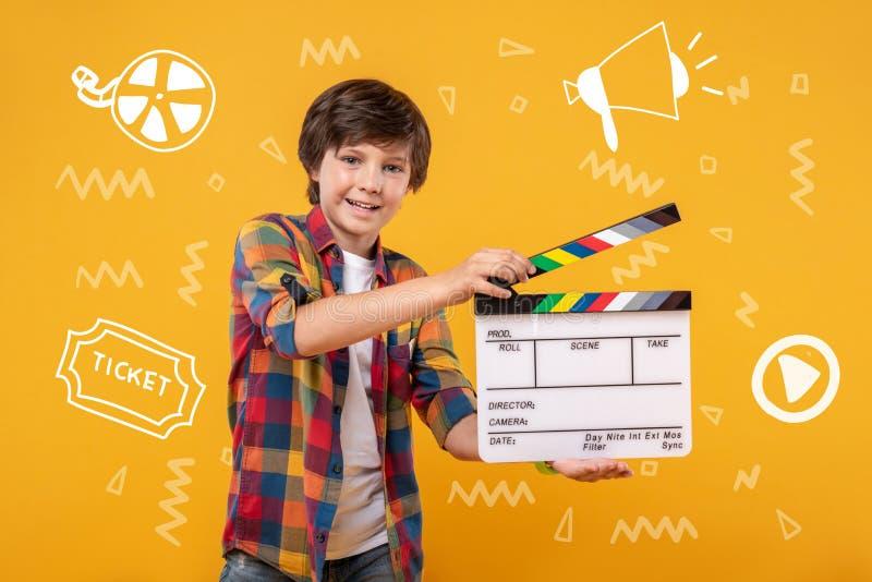 Tonårs- pojke som rymmer en clapstick och gör en amatörmässig film arkivbild