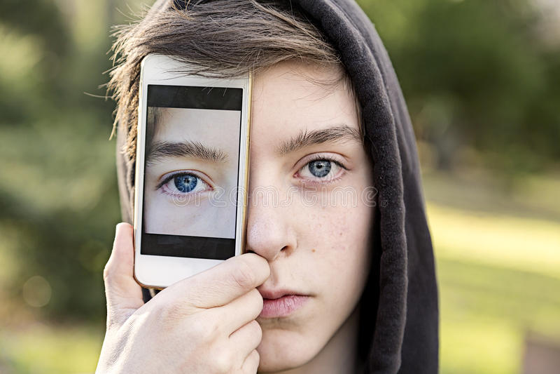 Tonårs- pojke som rymmer en smart telefon främst av hans framsida royaltyfri fotografi