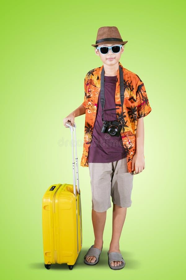 Tonårs- pojke som rymmer ett bagage i studion arkivfoton