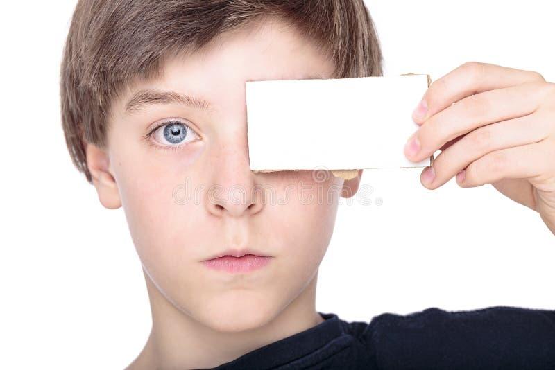 Tonårs- pojke som rymmer ett vitt stycke av papp arkivbild