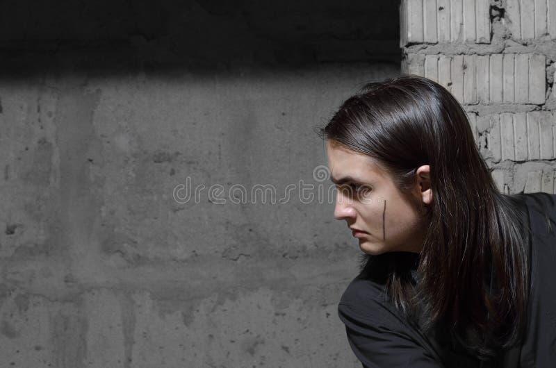Tonårs- pojke som smyga sig i den övergav byggnaden royaltyfri bild