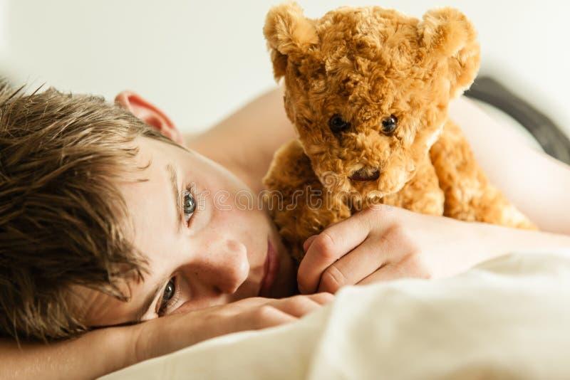 Tonårs- pojke som smyga sig på säng med bruna Teddy Bear royaltyfria bilder