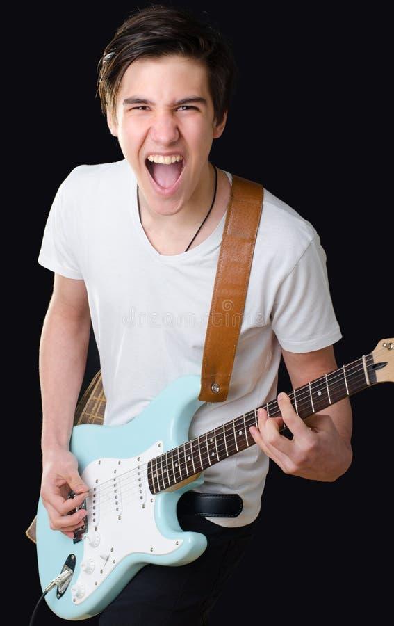 Tonårs- pojke som spelar den elektriska gitarren och att sjunga arkivbilder