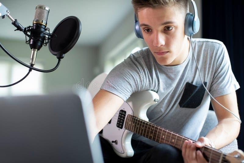 Tonårs- pojke som spelar gitarren och hemma antecknar musik på bärbara datorn royaltyfri foto