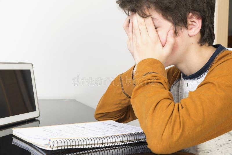 Tonårs- pojke som studerar med den hemmastadda digitala minnestavlan arkivbild