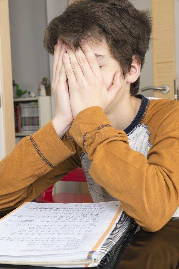 Tonårs- pojke som studerar med den hemmastadda digitala minnestavlan arkivfoton