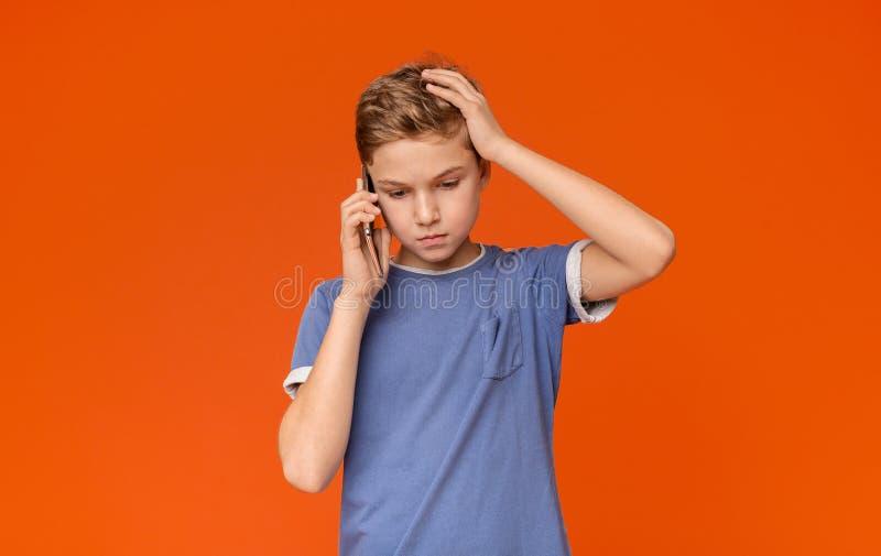 Tonårs- pojke som talar på telefonen som rymmer handen på huvudet i spänning fotografering för bildbyråer