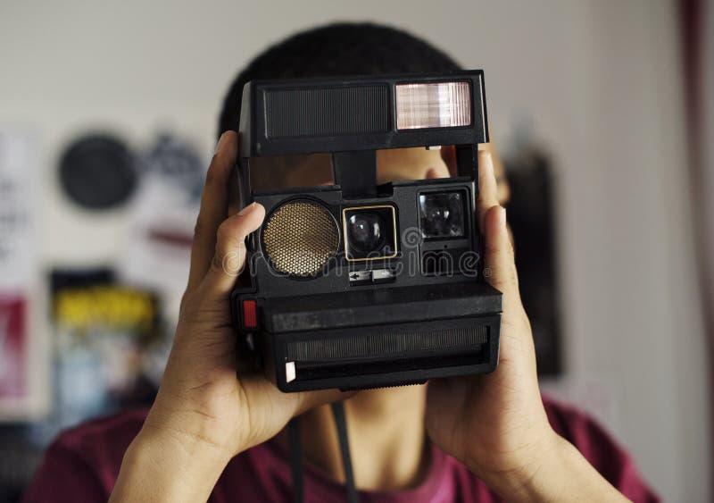 Tonårs- pojke som tar en bild i ett sovrumhobby- och fotografibegrepp royaltyfri bild