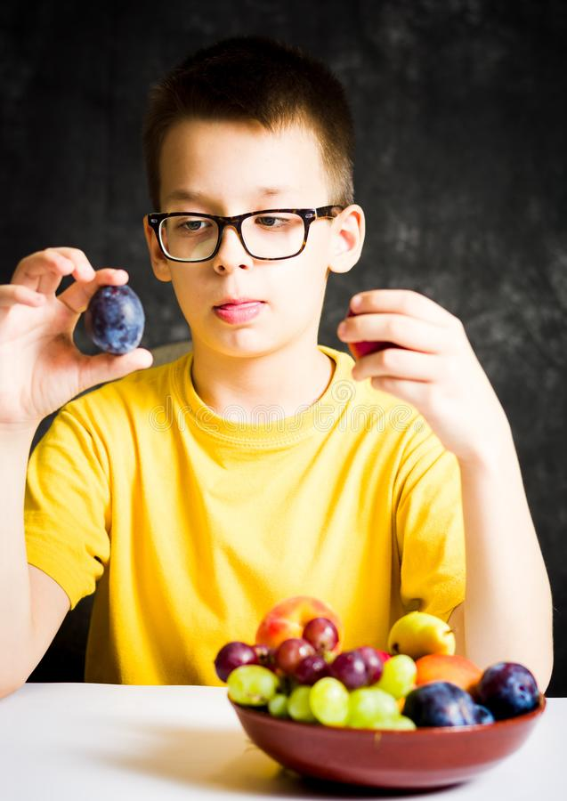 Tonårs- pojke som väljer mellan sort två av frukt arkivfoton